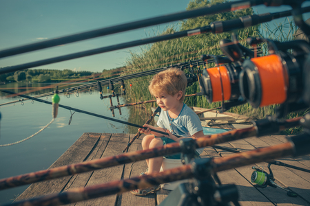 Summer vacation of little boy fishing on river.