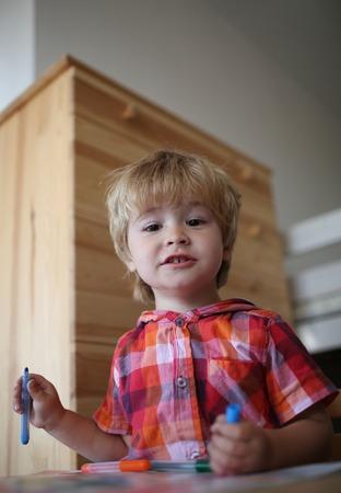 Kid or blonde happy boy paint with felt pen.