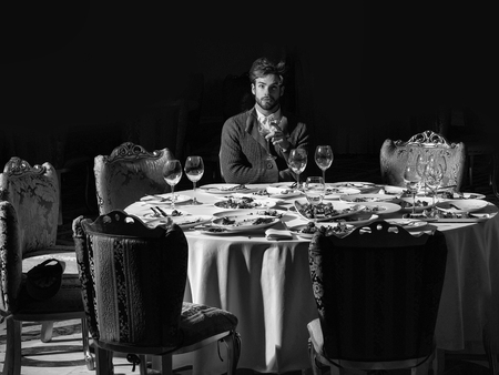 Handsome young man with beard and blond hair drinks wine from glass sitting at table with leftovers or residues food on dirty plates after banquet dinner