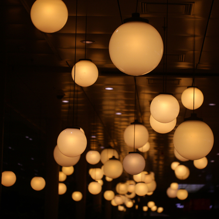 Ceiling lights of spherical shape on dark background. Lighting design, decor, interior. Round lamps shine indoor.