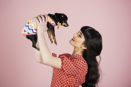 Happiness, positive emotion, smile, holiday, birthday, dog, pet concept. Woman receives present and smiles. Lady wears dotted dress and holds puppy. Happy girl with cheerful face on pink background. Stock Photo