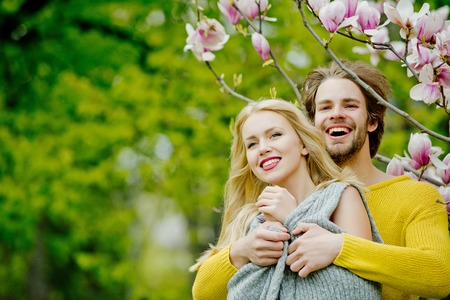 man and pretty girl or cute woman enjoying pink, magnolia flower blossom on trees in flowering, spring park on idyllic, sunny day on blurred floral environment. Daydreaming. Couple in love
