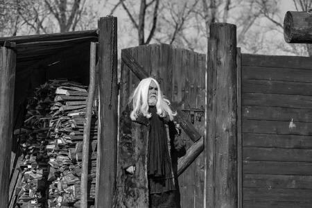 長い白い髪と木の背景に屋外で晴れた日に深刻な顔に深刻な顔にひげを生やしたドルイドの古いひげの男 写真素材