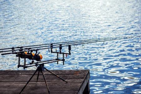 Spinning tackles on pod on wooden pier. Rods and reels at river or lake water. Fishing, adventure, sport, activity. Spin fishing, angling, catching fish. Summer vacation, pastime, hobby.