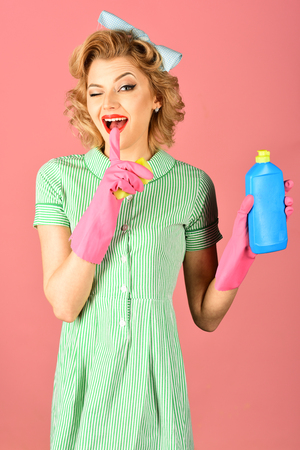 Pinup woman with cleaning set over pink background