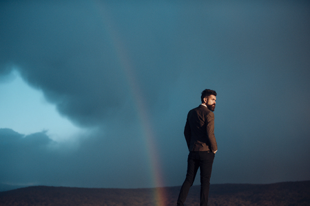 Guy with strict face in suit enjoy scenery and loneliness. Hipster with stylish appearance in front of sky with rainbow. Lonely stylish man with scenery on background. Alone in world concept. Stock Photo