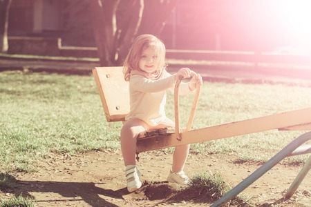 Girl smile on seesaw on sunny day. Child have fun on playground. Balance, equilibrium, harmony. Kid on teeter totter outdoor. Childhood, activity, lifestyle.