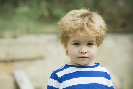 Child or boy with calm face wears striped clothes. Cute, adorable kid or son with untidy blonde hair on light background, defocused. Childhood concept.