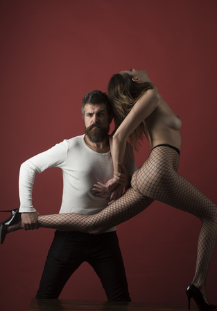 Lady in fishnet tights and nude breasts on burgundy background. Man with strict face holds woman, dont let her go. Dependence and slavery concept. Female as property of male, captivity, slavery. Foto de archivo