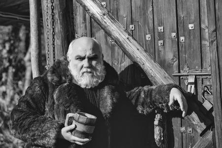 木製の背景に屋外の毛皮のコートで鉄の装飾と木製のカップを保持し、深刻な顔に長いひげを持つひげの男