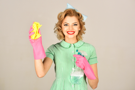 Pinup woman hold soup bottle, duster. Cleaning, retro style, purity. Housekeeper in uniform with clean spray, duster. Retro woman cleaner on grey background. Cleanup, cleaning services, wife, gender.