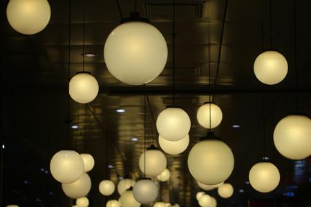 ラウンドランプは屋内で輝きます。暗い背景に球形の天井ライト。照明デザイン、装飾、インテリア。