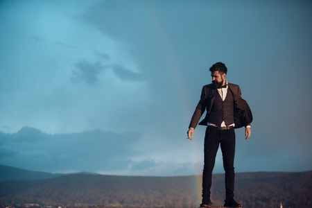 Guy with strict face in suit feels free and successful. Successful man with scenery on background. Hipster with stylish appearance smoking in front of sky with rainbow. Success and freedom concept.