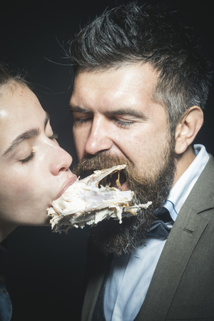 Man and woman with chickens skeleton in mouths on black background. Couple eats or bites chicken together with closed eyes. Enjoy your meal concept. Couple enjoys meal, meat or fowl.