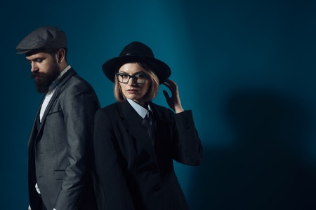 Man and woman in oldfashioned suit and hat on dark background. Couple of detectives or researchers, private investigators. Couple in love or work partners working together. Retro detective concept. Stock Photo