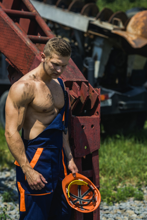 Sexy handyman concept. Handsome man or bodybuilder with strict face. Muscular builder holds hard hat, wears overalls. Sexy man with nude torso near construction equipment or excavator on background. Фото со стока