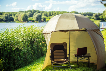 Fishing tent with armchair, laptop on summer landscape. Fishing umbrella at river or lake beach. Shelter, new technology, sunshade, waterproof, wind proof. Camp, picnic, angling activity.