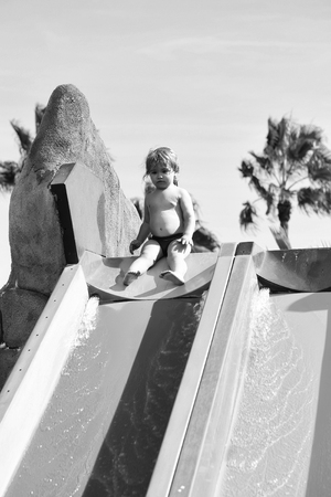 Cute baby boy with blond hair sits on top of colorful waterslide outdoors on sunny summer day on blue sky background Stock Photo - 96675702