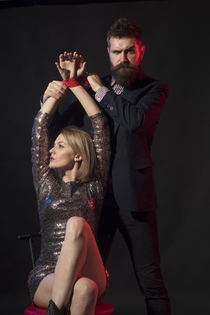 Couple in love on dark background. Drunk lady submissive and lets to tie her hands. Man and woman in fancy clothes after corporate party. Man with strict face binds hands of girl with tape.
