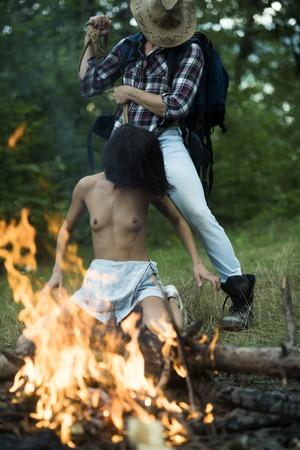 Seksueel misbruik concept. Ontvoerder of rover valt jong meisje aan met touw, dwingt kleding uit te trekken. Domineer man ontvoerd naakt meisje in bos nabij vreugdevuur, onscherp.