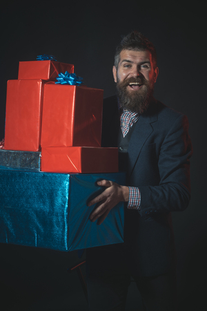 Man or businessman holds pile of gifts on black background. Hipster with beard and mustache in suit holds boxes and presents. Gifts and presents concept. Man with smiling face celebrates holiday.