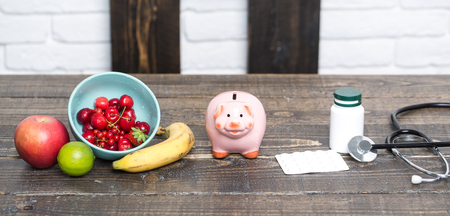 Piggy bank with fruit, medicine and stethoscope on table. Medical insurance concept. Medicine, pills, drug. Diet, health, vitamin. Food, supplement concept.