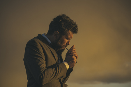 Man with beard and cigarette with dramatic sky on background. Guy with thoughtful face in luxury classic suit smoking. Hipster with stylish appearance smoke in front of sky. Smoking hipster concept. Reklamní fotografie