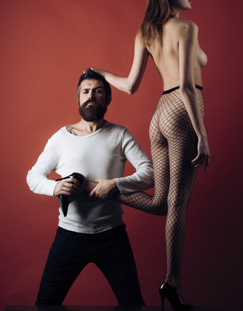 Man with strict face holds female leg and puts high heeled shoe on her foot. Lady in fishnet tights on burgundy background. Hipster found sexy naked Cinderella, copy space. Sexy Cinderella concept.