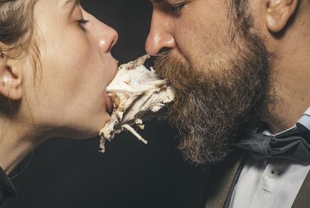 Paar geniet van maaltijd, vlees of gevogelte. Man en vrouw met kippenskelet in monden op zwarte achtergrond. Paar eet kip samen. Geniet van uw maaltijdconcept. Rare esthetiek, nabijheid en intimiteit.