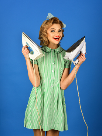 Housekeeper in uniform with iron, household. housekeeper woman ironing on blue background