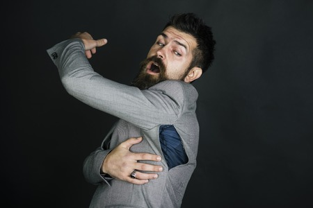 Hipster chose small size jacket, seam torn under armpit. Man with beard wears jacket with hole on dark background. Bad quality of clothes concept. Surprised guy bought counterfeit or fake brand. Stock Photo