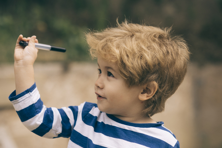 Child or boy with smiling face wears striped clothes. Childhood concept. Cute, adorable kid or son with untidy blonde hair on light background, defocused. Boy holds or plays with pen or marker in hand