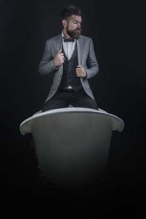 Concepto de artículos sanitarios de alta calidad. Hipster con aspecto elegante en la bañera de lujo a la antigua. Hombre o vendedor de productos sanitarios sobre fondo oscuro. Chico con cara estricta en traje se sienta en la bañera. Foto de archivo - 96678021