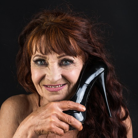 Happy lady with black high heel shoe, fashion. Senior woman smile with wrinkled face skin, makeup, dyed hair, beauty. Fashion, beauty, look, hairstyle.