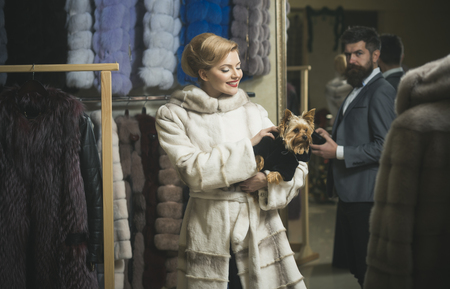 Man with strict face and woman with coats in fur shop. Money and style concept. Woman in fur coat with dog and man in shop. Couple in love holds white sable and chinchilla fur coats.