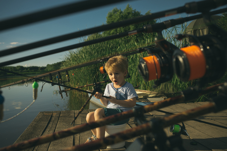 Cute little boy fishing on pond on summer day.