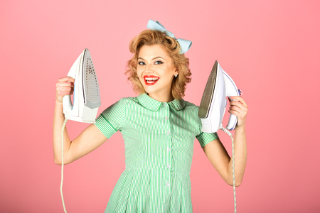 A smiling housekeeper in retro uniform with two irons, household concept Foto de archivo - 106574326