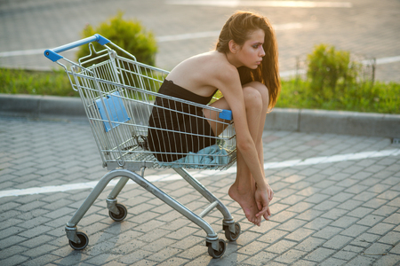 Young beautiful brunette woman sits in empty shopping cart.