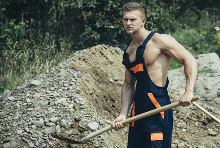 Muscular builder on sunny day work at construction site