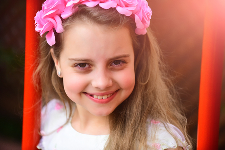 Little girl with flower in hair, childhood and happiness. Girl child with pink flowers in hair spring. summer fashion, beauty salon. Hairdresser and hairstyle. Fashion, spring, look. Stock Photo