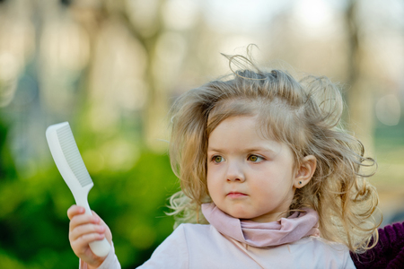 Kid with long blond hair hold comb on natural background. Girl beauty, look, hairstyle, care, health. Child, childhood, playtime, lifestyle concept. 版權商用圖片
