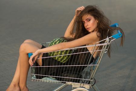 Shopping, shop, shopaholic. Girl shopper with watermelon sit in shopping cart. Fashion woman, beauty, look, makeup, hair. Sale, purchase, black Friday. Vegetarian food, diet, health, vitamin.