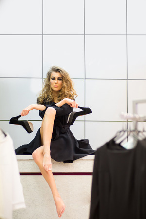 Girl with black high heel shoes in dressing room, fashion. Woman with makeup face, long hair, beauty in shop. Fashion, style, vogue. Beauty, look, make up. Shop, shopping, purchase.