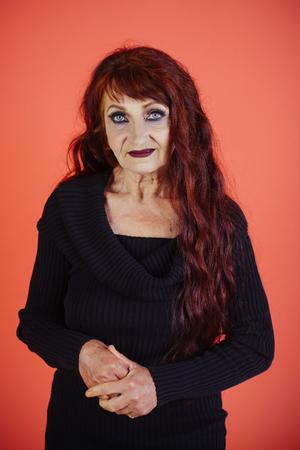 長い染めた髪の色、髪型を持つ女性。しわのあるシニアモデル、老化肌、化粧、見た目。アンチエイジング、若返り、持ち上げ。スキンケア、スキ
