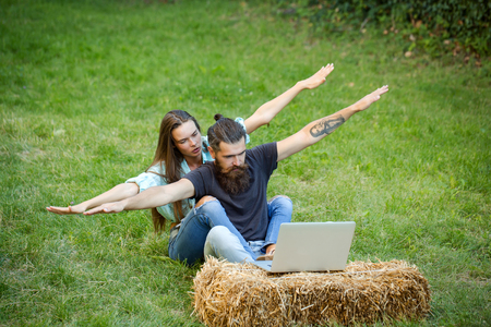 agile business, youth. Bearded man and sexy woman on green grass, vacation. Couple in love use laptop on nature, internet surfing. New technology, modern life. Love, relations, couple, happy family.