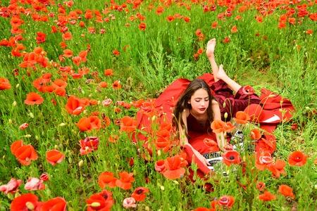 Woman writer in poppy flower field. woman writer with typewriter in poppy field