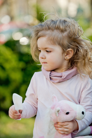 Child with long blond hair hold comb and toy horse on natural background. Girl beauty, look, hairstyle, care, health. Childhood, playtime, lifestyle concept.