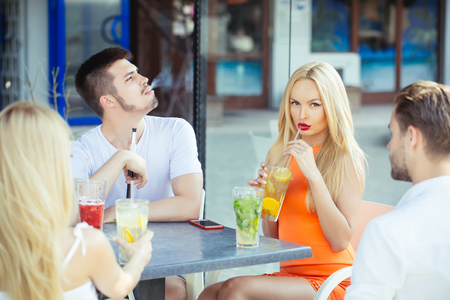 Bad habits, party, addiction. Man vapor hookah pipe in shisha bar lounge. Women twins and men friends relax in cafe outdoor. Celebration, party, proposal, birthday. Stock Photo
