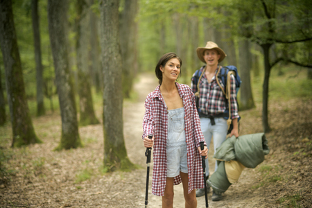 Couple in love hiking in forest with touristic equipment, trees on background, defocused. Young couple with happy faces walks. Man with woman hiking with overnight stay or picnic. Tourists concept. Stock Photo
