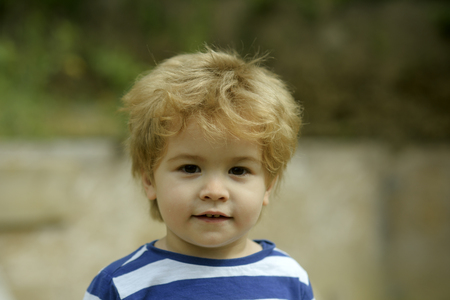 Childhood concept. Child or boy with calm face wears striped clothes. Cute, adorable kid or son with untidy blonde hair on light background, defocused.